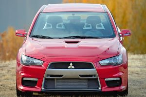Red Mitsubishi Evo X Front View In Field